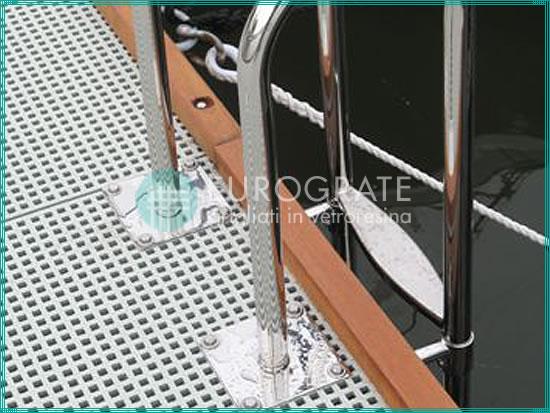 suelo de rejilla y escaleras verticales para subir y bajar a una embarcación atracada en un puerto