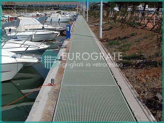 pasarela de rejilla instalada en una zona costera con amarres para los yates